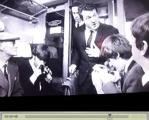 Still from Hard Days night. George looks into bag while John snorts Pepsi.