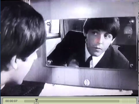 Still from A Hard Days Night: Paul looks into the mirror.