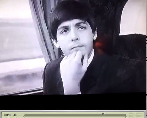 Still from A Hard Days Night: Paul puts his hand on his chin, fingers back.