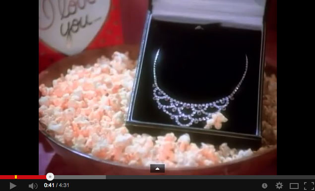 Still from Madonna's Material Girl video showing a diamond necklace in a bowl of popcorn.